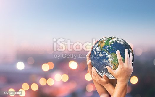 Human hands holding earth global over blurred blue nature background. Elements of this image furnished by NASA (https://earthobservatory.nasa.gov/images/885)