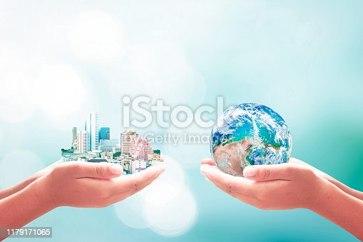 Two human hands holding earth global and big city on blurred blue nature background. Elements of this image furnished by NASA