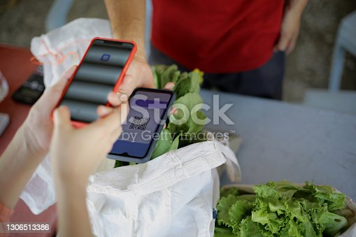 An Asian woman is using contactless payment for shopping fresh vegetable from local farmer.