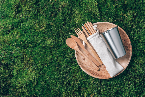 Sustainable lifestyle. Zero waste, plastic free, recycling concept. Stainless steel cup, wooden spoon, fork, knife, lunch plate and drinking bamboo straw on green grass, moss background.