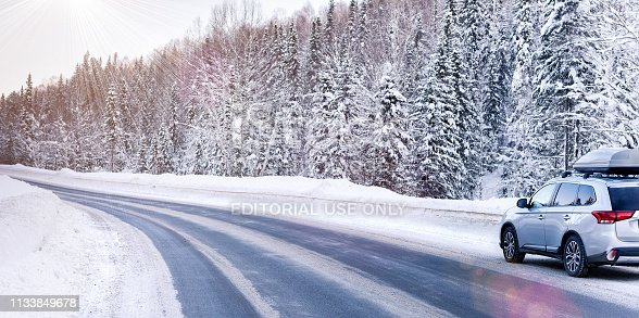 istock Suv car with rooftop cargo carrier trunk stay on roadside of winter road. Family trip to ski resort. Winter holidays adventure. car on winter road 1133849678