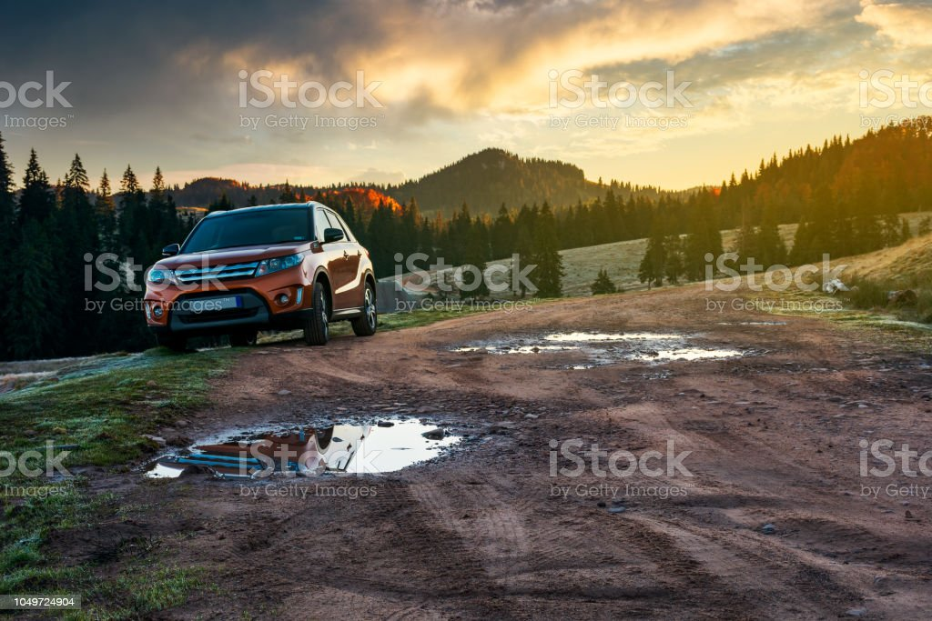 suv parked on the road near forest at sunrise orange suv parked on the country road near forest in mountains at sunrise. beautiful autumn scenery. travel Europe by car concept 4x4 Stock Photo
