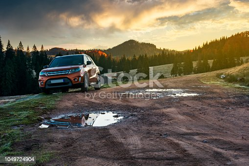 istock suv parked on the road near forest at sunrise 1049724904