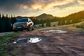 orange suv parked on the country road near forest in mountains at sunrise. beautiful autumn scenery. travel Europe by car concept