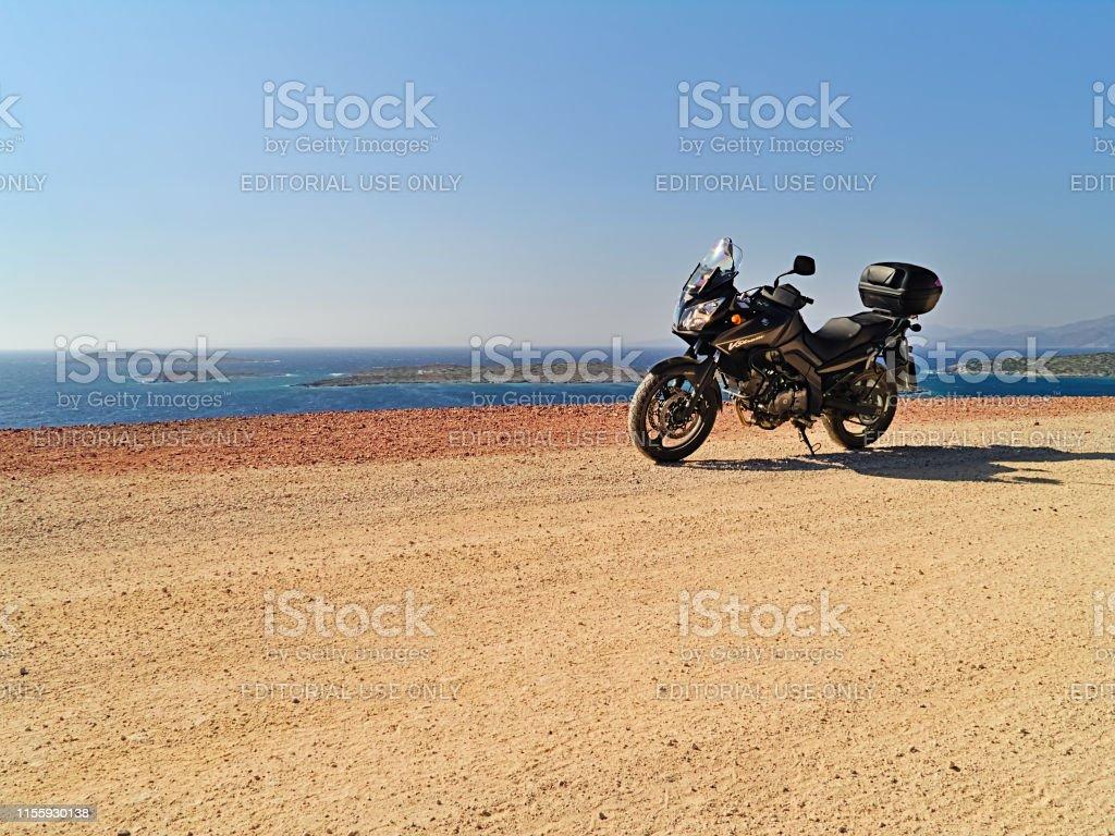 Suzuki dl650 motorcycle on dirt road near the sea, sunny summer day.