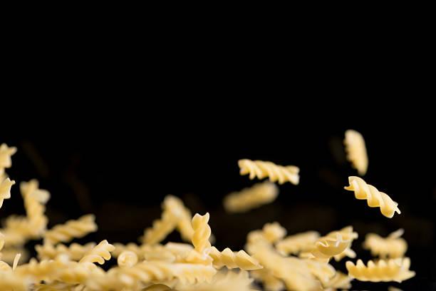 sveral flying spiral noodles on black background – Foto
