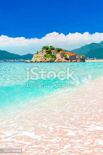 Sveti Stefan small island with red-tiled roofs, green trees, bright blue sky with white clouds and beautiful sandy Adriatic sea Montenegrobeach,Budva municipality. Vertical summer tourist background