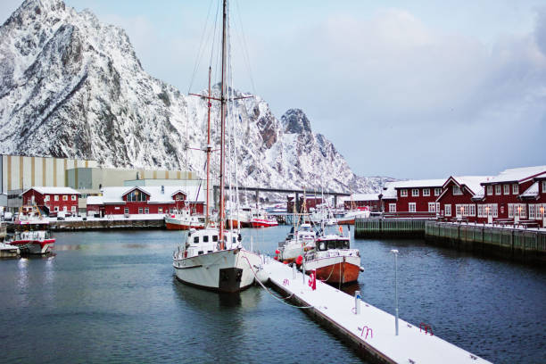 Svolvaer harbor with boats and red rorbu with snowy mountains on background. stock photo