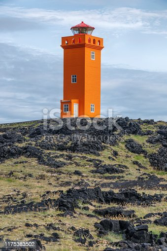 A lighthouse painted a bright orange.