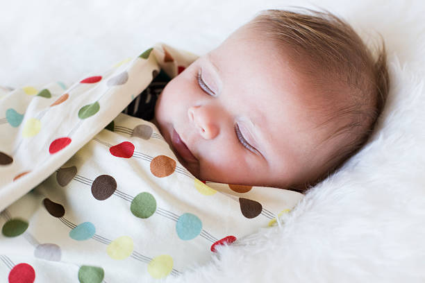 Swaddled sleeping Baby boy Beautiful photo of a male new born baby, wrapped in a coloured poka dot blanket, with a white background. baby blanket stock pictures, royalty-free photos & images