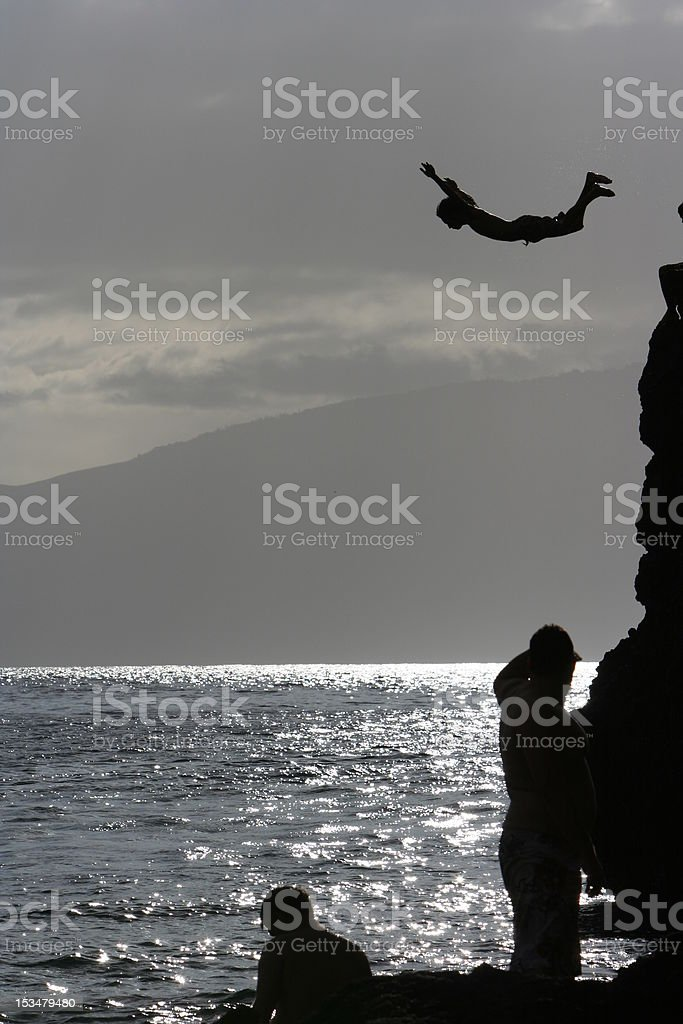 Swan Dive Into The Ocean, cliff diving in hawaii stock photo
