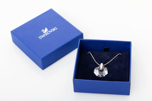 Mexico City, Mexico - August 10, 2013: Swarovski crystal pendant inside a jewelry box with the brand's signature blue color, on white background