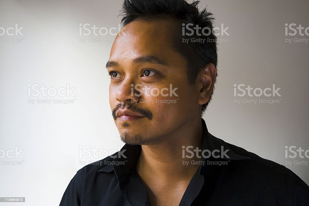 Swarthy man in a black shirt is thinking stock photo