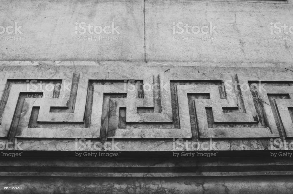 Swastika continuous ornament, carved on a stone wall. Black and white picture. stock photo