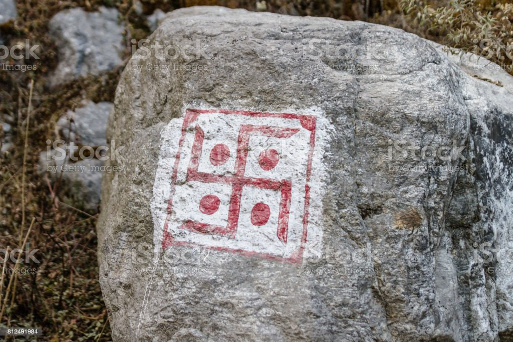 Swastika sign on grey stone at Thangu and Chopta valley in winter in Lachen. North Sikkim, India. stock photo