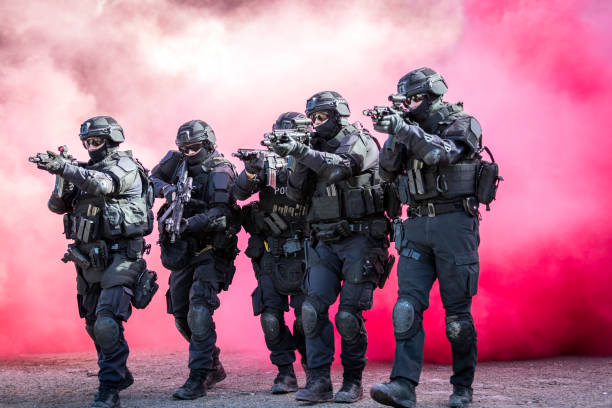 Swat Police Officers Shooting With Firearm Swat Police Officers Shooting With Firearm while crossing a red smoke wall counter terrorism stock pictures, royalty-free photos & images