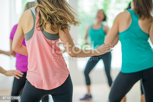 A multi-ethnic group of adult women are taking a dance fitness class indoors. They are wearing casual, colourful sports wear. They have their backs to the camera while dancing.