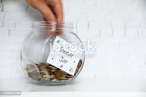 Glass Jar on a white shelf in a household living room. Swear box Concept