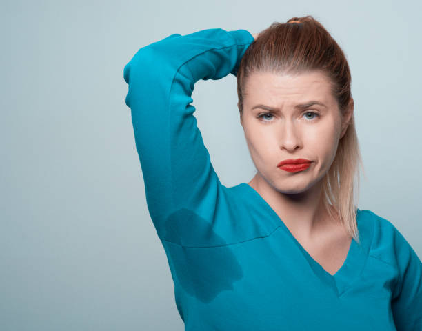 sweat issues confused and negative expression of young woman with her arm raised with her armpits sweat.looking at camera and frowning. wet clothing women t shirt stock pictures, royalty-free photos & images