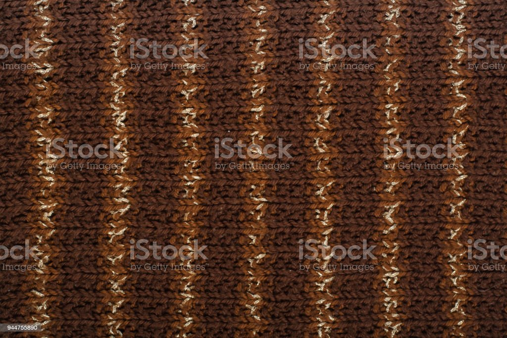 Sweater or scarf fabric texture large knitting. Knitted jersey background with a relief pattern. Wool hand- machine, handmade, brown