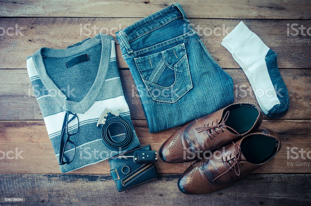 Sweaters, jeans, socks, shoes, belts, wallets, sunglasses, ready for travel. royalty-free stock photo