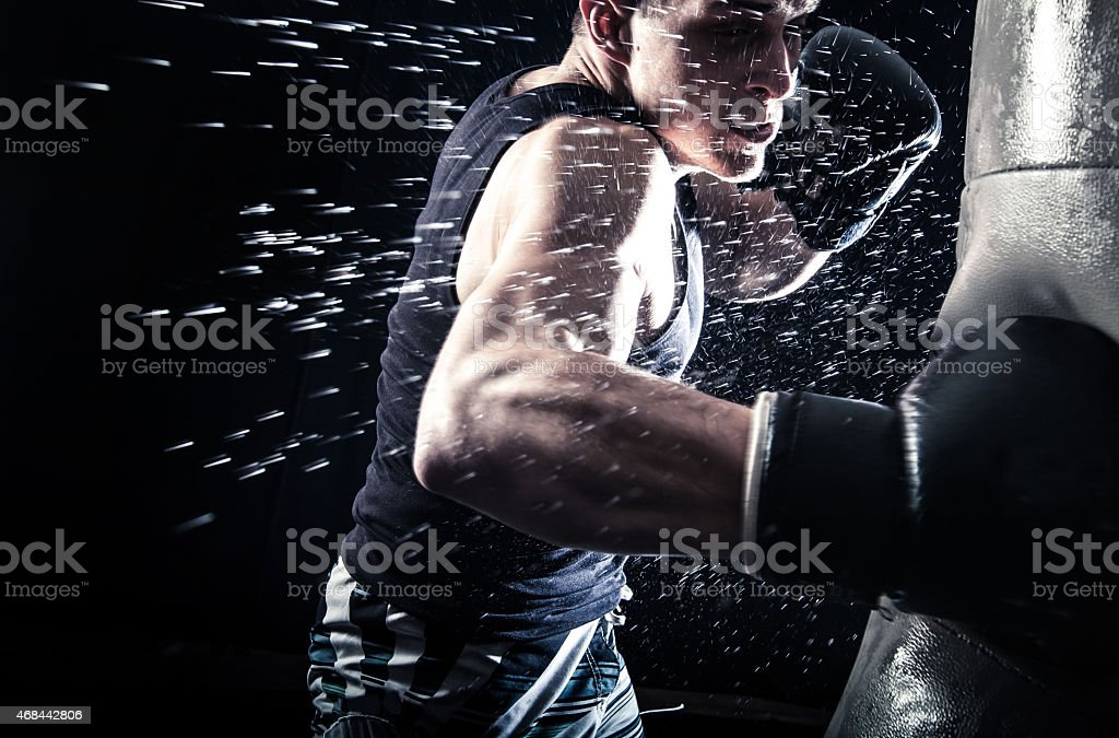 Sweating boxer punching a black bag on black background stock photo