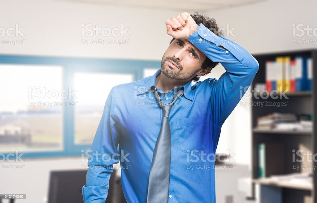 Sweating businessman due to hot climate stock photo