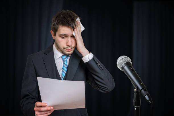 Sweating nervous speaker is afraid of public speech. Microphone in front. stock photo