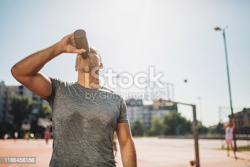 Middle aged man exercising on a sports court.