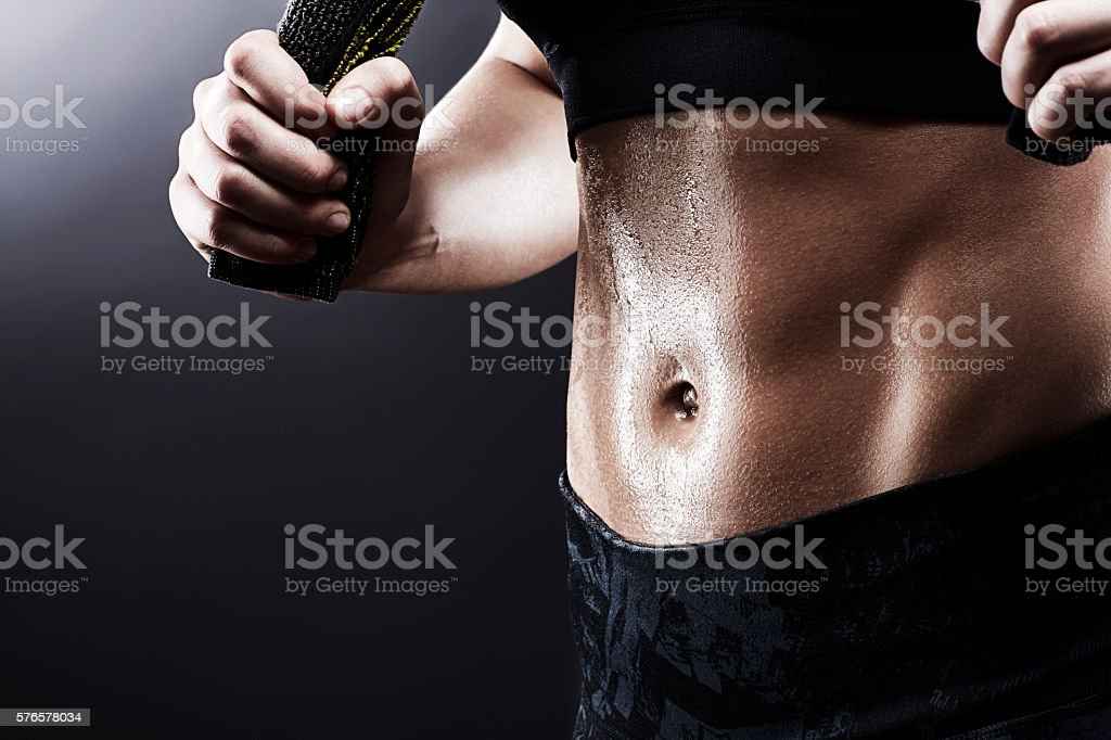 Sweating sporty young woman with perfect abs holding towel stock photo