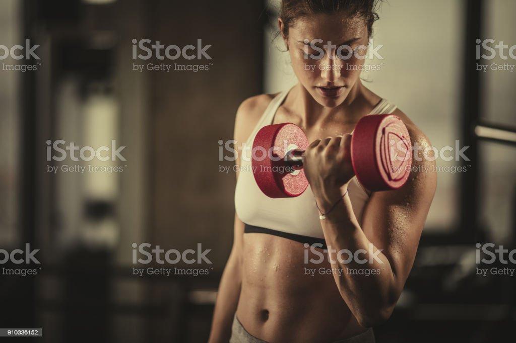 Schweißtreibende sportliche Frau mit Hanteln im Fitnessstudio trainieren. – Foto