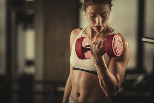 sweaty athletic woman exercising with dumbbells in a health club. - dumbbell stock pictures, royalty-free photos & images