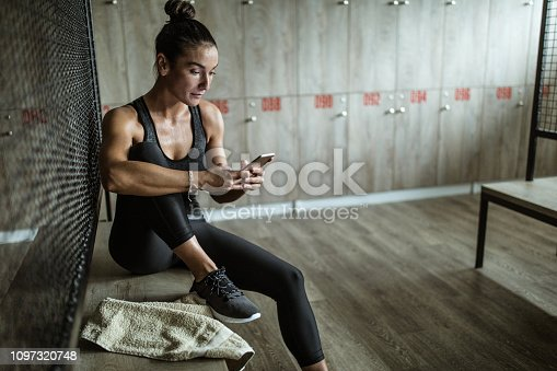 Young athletic woman using mobile phone after sports training at gym's dressing room.