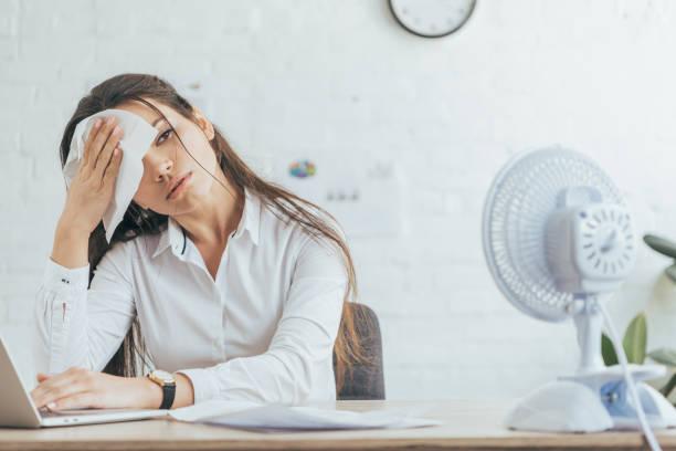 verschwitzten geschäftsfrau arbeiten im Büro mit Elektrolüfter – Foto