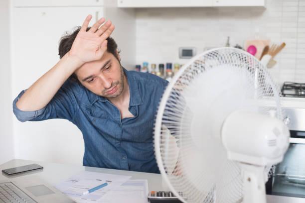 Sueur homme essayant de se rafraîchir de la chaleur avec un fan - Photo