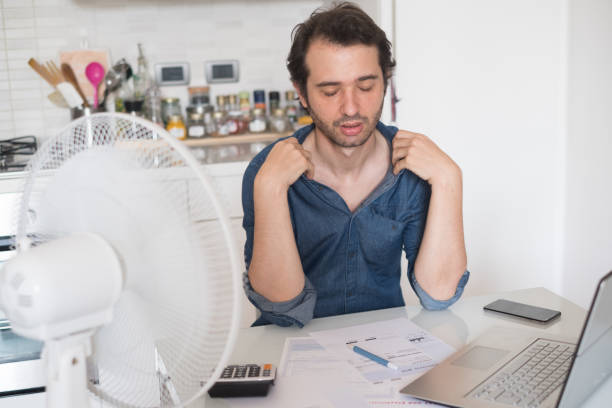 sweaty man trying to refresh from heat with fan - heat haze stock pictures, royalty-free photos & images