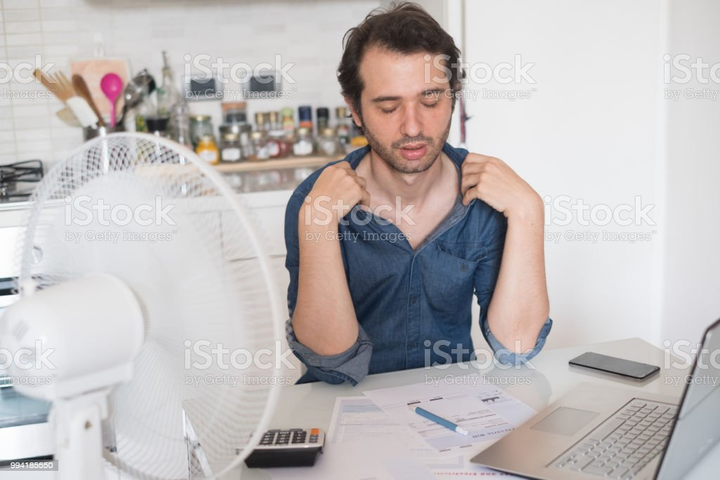 Sweaty man trying to refresh from heat with fan stock photo