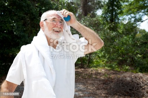 Sweaty senior man holding a racquetball and wearing safety glasses, dries himself with a towel.