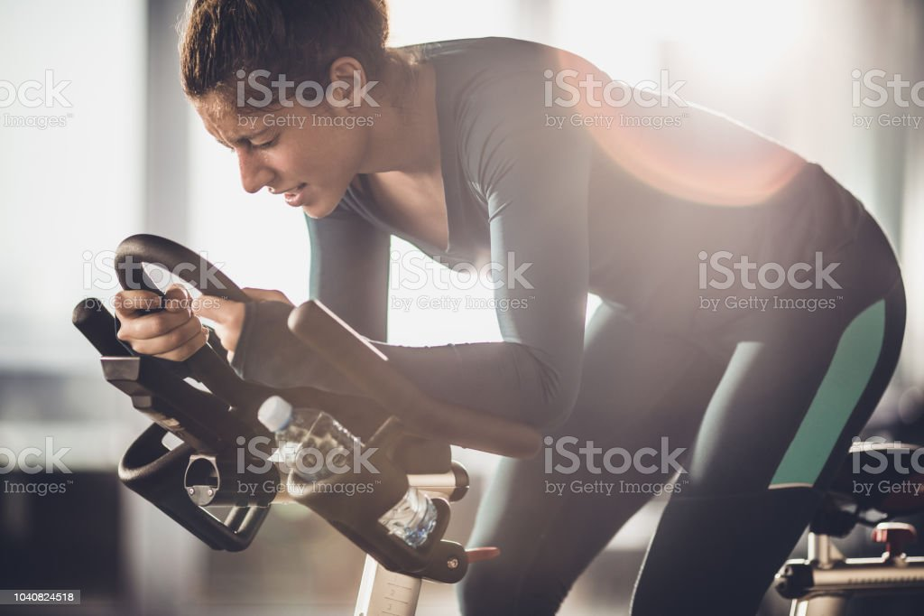 Determined female athlete making an effort on a spinning class in a...