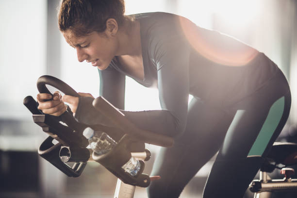verschwitzte frau bemüht sich beim radfahren mit dem fahrrad in einem fitnessstudio. - herumwirbeln frau stock-fotos und bilder