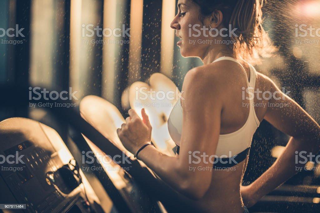 Femme en sueur qui court sur tapis roulant au cours de la formation en gymnastique sportive. - Photo
