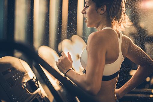Foto de Mulher Suada Correndo Na Esteira Durante Treinamento Em Um Ginásio Esportivo e mais fotos de stock de Academia de ginástica