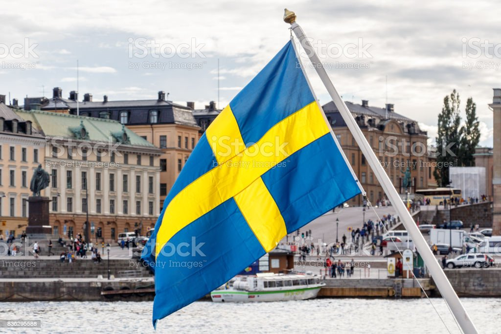 Sweden flag and Stockholm old town Gamla Stan in background stock photo
