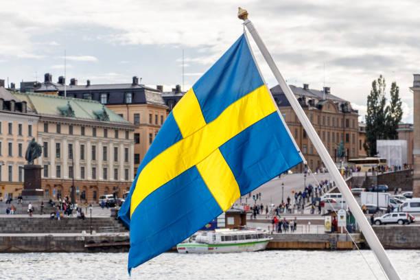 sweden flag and stockholm old town gamla stan in background - szwecja zdjęcia i obrazy z banku zdjęć
