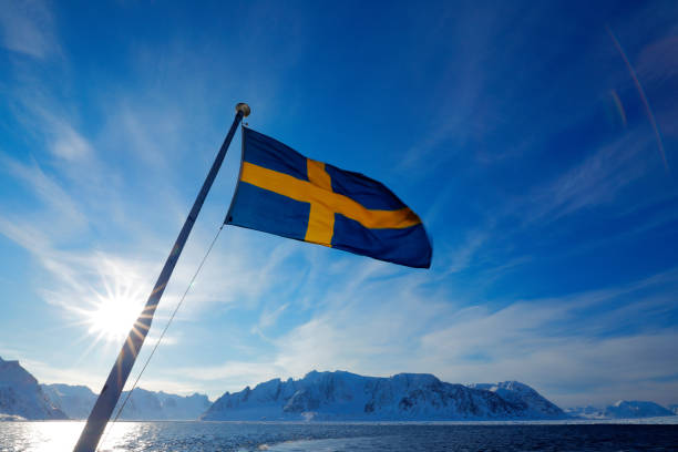 Sweden flag with blue sky. Rocky island with snow. White snowy mountain, blue glacier Iceberg twilight, ocean. Pink clouds with ice floe. Beautiful landscape. Land of ice. Cold blue water nature. stock photo