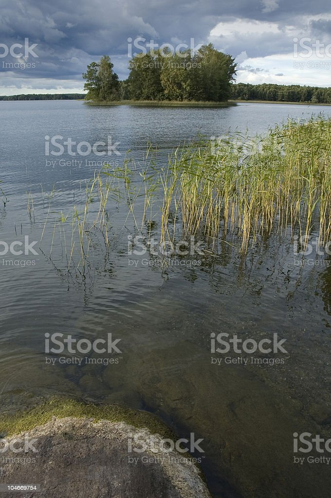 Sweden, islet in a lake under stormy weather royalty-free stock photo