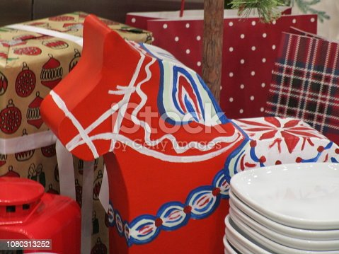 The traditional Dalarna horse stands in front of some wrapped presents.