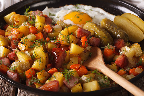 Swedish cuisine: pyttipanna with fried egg and pickled cucumbers stock photo