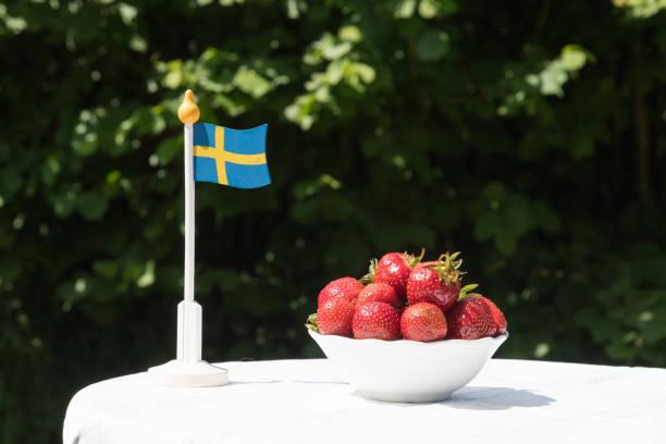 Morangos e bandeira sueca - foto de acervo
