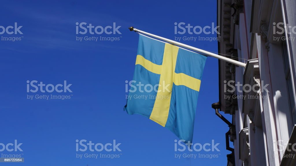 Swedish flag hanging from building stock photo